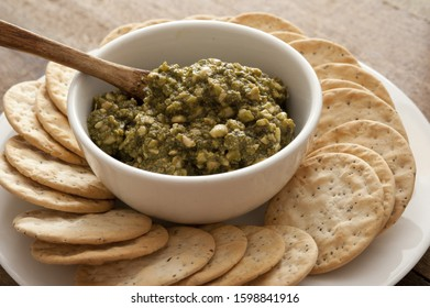 Water biscuits or crackers arranged on a plate around a bowl of pesto nut dip for a tasty healthy snack or appetizer