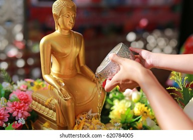 Water blessing ceremony for Songkran Festival or Thai New Year. Women and child girl paying respects to a statue of Buddha by pouring water onto it.
