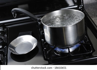 Water boiling in a stainless steal pot on a black stove.