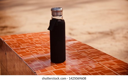 A water bottle with black covers kept on a tiles surface