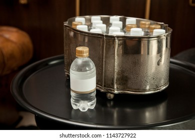 water bottle with blank label, with an ice bucket in the background on a fancy room.