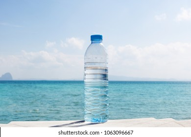 Water bottle on tropical beach. Hydratation and drinking regime. Health and fitness.
