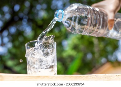 water from bottle pouring into glass on table, bokeh background. clean water for a good health.