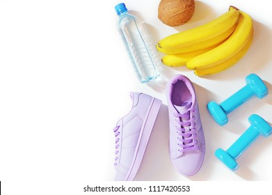 Water bottle, purple sneakers, coconut, a bunch of bananas and blue dumbbells on a white background. Flat lay fitness items, healthy lifestyle concept. Gym, fitness accessories and proper nutrition