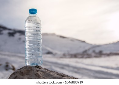 Water bottle with snowy mountain peak background.