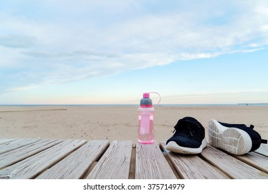 water in the bottle and sport shoes on the beach