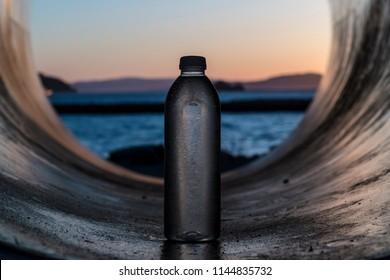 Water bottle in sundown in pipe