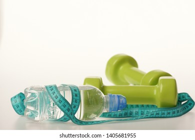 Water bottle tied with cyan measure tape by green dumbbells on white background, copy space. Diet and sport regime concept. Bottle wrapped with ruler by lightweight barbells. Healthy regime equipment