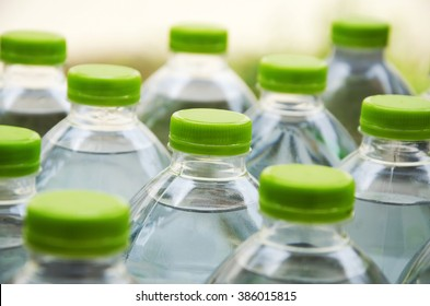 Water bottles with caps made of green plastic.