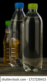 Water bottles and juice isolated on a black background.