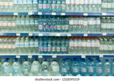 Water bottles product on shelves in supermarket blur background.