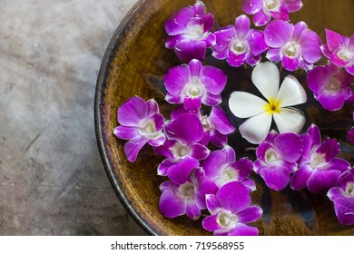 Water bowl with orchid flowers on rustic background, top view. Spa or wellness concept