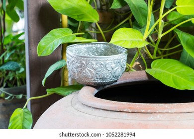 Water bowl and pottery jar, these objects are observed in traditional, native ways of living, especially in remote part of all regions in Thailand, Asia; selective focus and copy space.