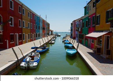 Water canal in Burano shot symmetrically with motorboats and colorful buildings aimed to the open sea