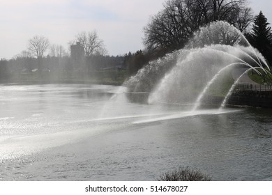 Water canons shooting into a river with trees in the background