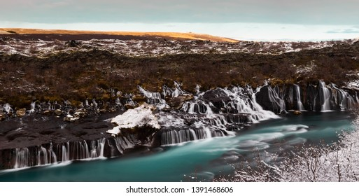 Water cascades over lava rock formations into a turquoise blue river in a winter scene. Hraunfossar Waterfall, Iceland.