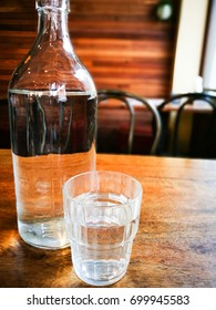 Water in the clear glass bottle and glass on the table in a restaurant.