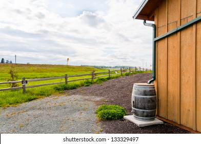 Water Conservation : Wooden Rain Barrel collecting runoff from roof through gutters. Copy space.