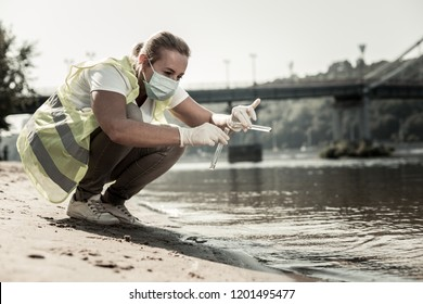 Water contamination. Professional sanitary inspector holding test tubes with water while checking water contamination level