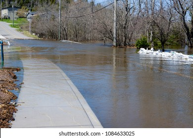 Water covering a flooded road. The yellow dividing line and sidewalk can be seen submerged. Trees in the background. Sandbags on the right.