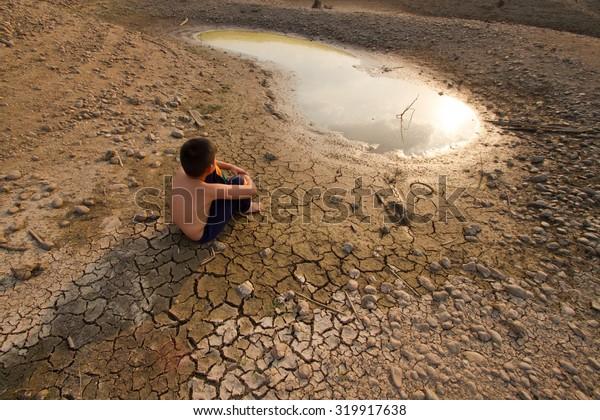 Crisis de agua, niños sentados en tierra agrietada cerca del agua secada.