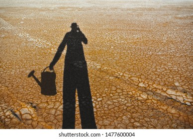 Water crisis and climate change depicted in the form of the shadow of a person searching for water in the desert or trying to water flowers in the desert