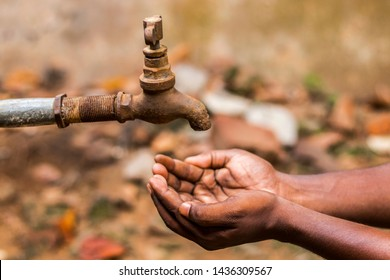water crisis is a serious threat to India and worldwide,a man holding his hand under the tap for water