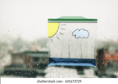 water cycle in a bag. a ziplock plastic bag with water and painted on it with a cloud and the sun hanging in the window. clouds form and rain fall in the bag. science experiment for children