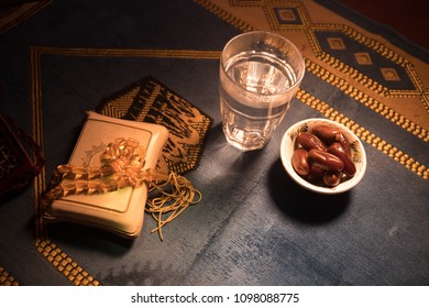Water and dates. Iftar is the evening meal. View of decoration Ramadan Kareem holiday on carpet. Festive greeting card, invitation for Muslim holy month Ramadan Kareem. Selective focus