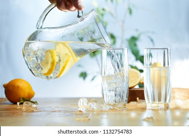Water from a Decanter with sliced lemon, ice poured into a glass.