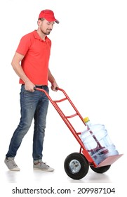 Water delivery. Cheerful young deliveryman holding a water jug while isolated on white