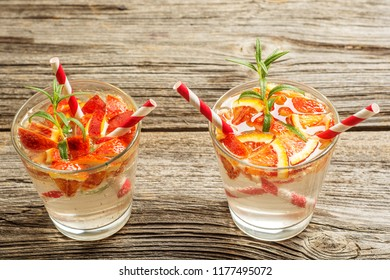 Water detox with orange and rosemary on old wooden background as lemonade refreshment. space for text