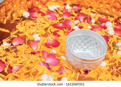 Water dipper with colorful flowers in water mixed perfume for Songkran day festival, Thailand.