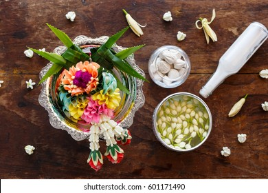 Water in water dipper with colorful flowers pedestal for Songkran festival, Thailand,Vintage