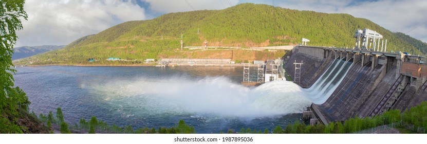 Water discharge to hydroelectric power station in Krasnoyarsk, Russia. Industrial landscape with Krasnoyarsk Dam at sunny day. Powerful water flow
