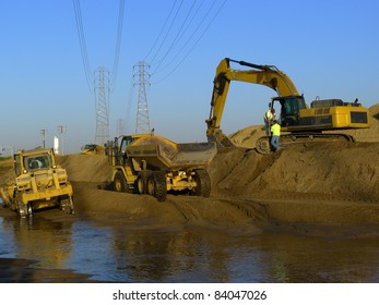 Water is diverted while construction equipment is used to widen and deepen a river bed