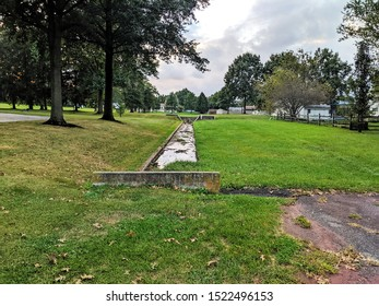 Water Drainage Easement with Water in Ditch and Green Grass on All Sides and Small Patch of Asphalt Blacktop and Trees in the Distance