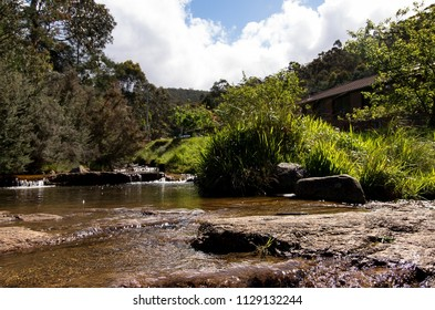 Water drifts a natural rock dam, dropping from a slight waterfall beside lush grass and the outline of a house set against the forest