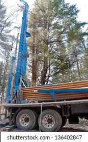 A water drilling rig is set up ready for use. Stacked against the rig are numerous casings for the well.