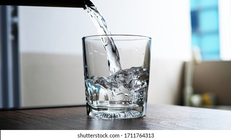 water to drink poured into a glass.