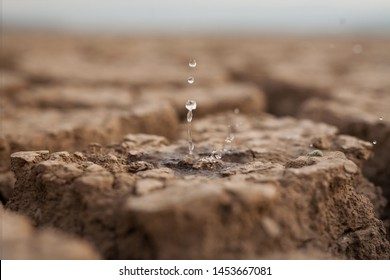 Water drop to dry cracked land metaphor lack of rain, water crisis, Climate change and Environmental disaster