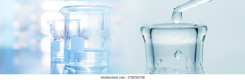 water drop into research glass flask and beaker in soft blue light medical science laboratory banner background