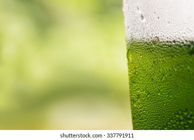 Water drop on plastic bottle of drink with green background background