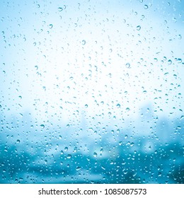 Water drop texture background of rain on glass window outside with rainy day or spring. Nature with sky cloud at city moisture droplet with blurred blue color abstract pattern.