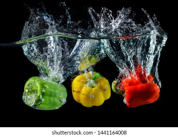 Water droping bell pepper or paprika with splashing water in black background.