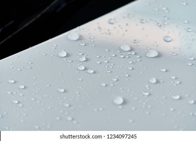 Water droplet on the car hood. Water beading after rain or car wash on white shiny paint surface. Beading created by ceramic coat or paint sealant with high surface tension. Water drop Backgroud.