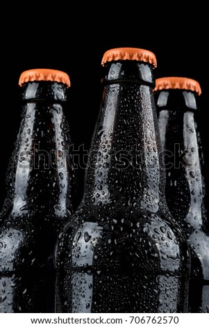 Water droplets on cold beer bottles with black background