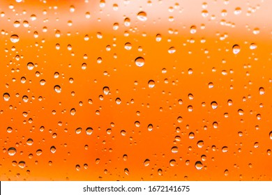 Water droplets from a rain shower on glass with an orange background.