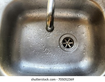 Water droplets in stainless steel sink.
