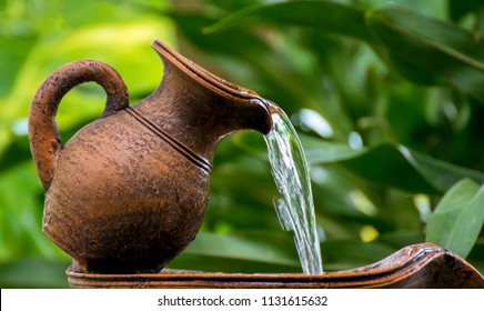water is dropping from clay jug in the garden.